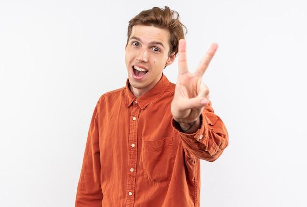 Opgewonden jonge knappe kerel met een rood shirt met een vredesgebaar dat op een witte muur wordt geïsoleerd
