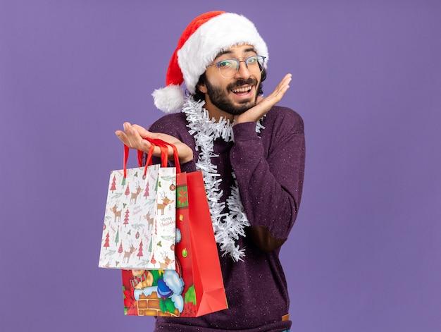 Opgewonden jonge knappe kerel met kerstmuts met slinger op nek houden geschenkzakken spreidende handen geïsoleerd op blauwe achtergrond