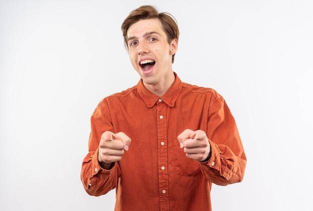 Opgewonden jonge knappe kerel met rode hemd wijst naar de camera