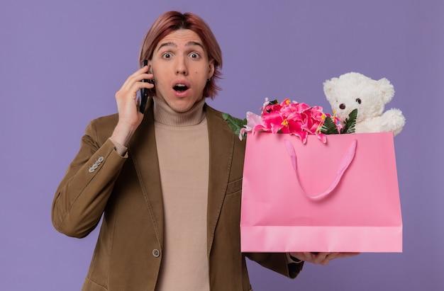 Opgewonden jonge knappe man die aan de telefoon praat en een roze cadeauzakje met bloemen en teddybeer vasthoudt