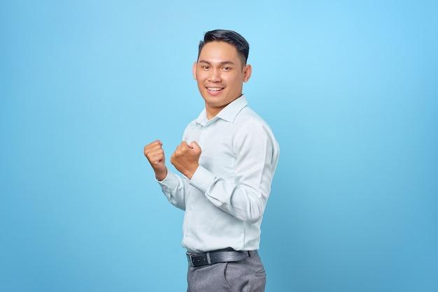 Opgewonden jonge knappe zakenman die succes viert met opgeheven hand op blauwe achtergrond
