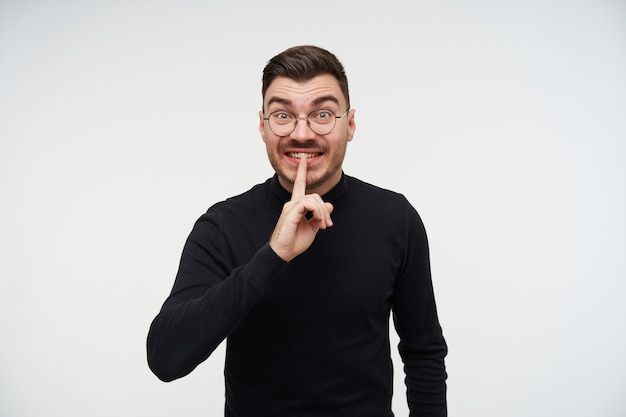 Opgewonden jonge kortharige bebaarde brunette man hand opsteken met stil gebaar en opgewonden kijken, zwarte trui dragen terwijl staande op wit
