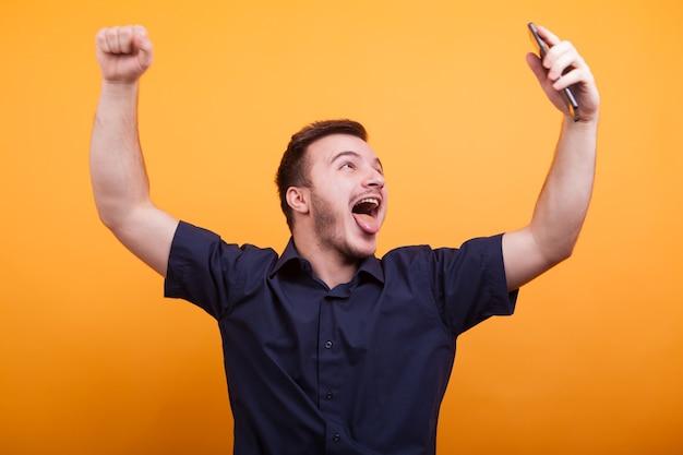Opgewonden jonge man die zijn armen op een gele achtergrond opheft