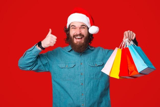 Opgewonden jonge man houdt een aantal boodschappentassen en duim opdagen op rode achtergrond.