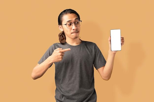Opgewonden jonge man in grijze tshirt presenteren smartphone en wijzend met de vinger