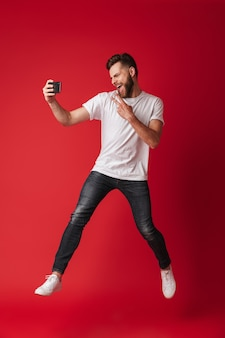 Opgewonden jonge man maakt selfie door mobiele telefoon te springen.