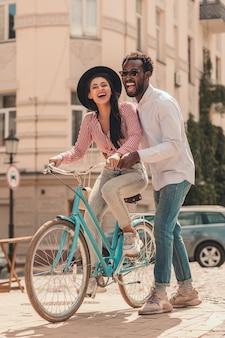 Opgewonden jonge man met vrouw op de fiets in de straat