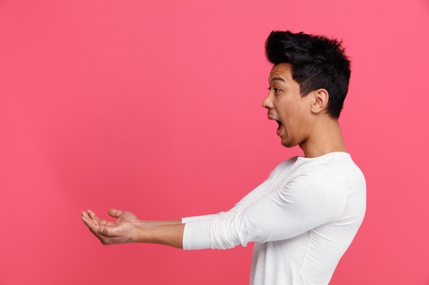 Opgewonden jonge man permanent in profiel te bekijken kant handen uitrekken