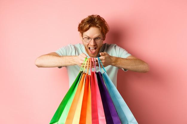 Opgewonden jonge man, shopper die boodschappentassen vasthoudt en gelukkig glimlacht, opgewonden kijkt naar gekochte artikelen, staande over roze achtergrond