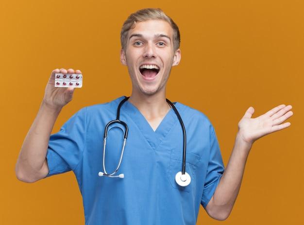 Opgewonden jonge mannelijke arts die artsenuniform met de pillen van de stethoscoopholding draagt die hand verspreiden die op oranje muur wordt geïsoleerd