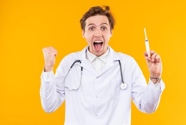 Opgewonden jonge mannelijke arts die een medisch gewaad draagt met een stethoscoop die een spuit vasthoudt en een ja-gebaar toont
