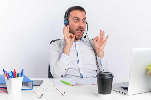 Opgewonden jonge mannelijke callcentermedewerker met een headset die aan tafel zit met kantoorhulpmiddelen die naar een laptop kijken die een goed gebaar toont