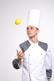Opgewonden jonge mannelijke chef-kok of bakker man in wit uniform overhemd poseren geïsoleerd op witte muur achtergrond studio portret. koken voedsel concept. bespreek kopie ruimte. citroen in een hand houden.