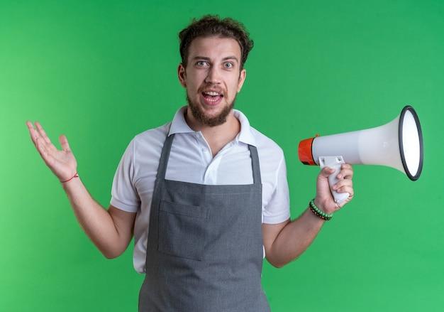Opgewonden jonge mannelijke kapper die een uniforme luidspreker draagt die de hand verspreidt, geïsoleerd op een groene muur