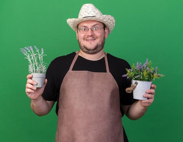 Opgewonden jonge mannelijke tuinman die tuinieren hoed draagt ?? die bloemen in bloempotten houdt die op groene muur worden geïsoleerd