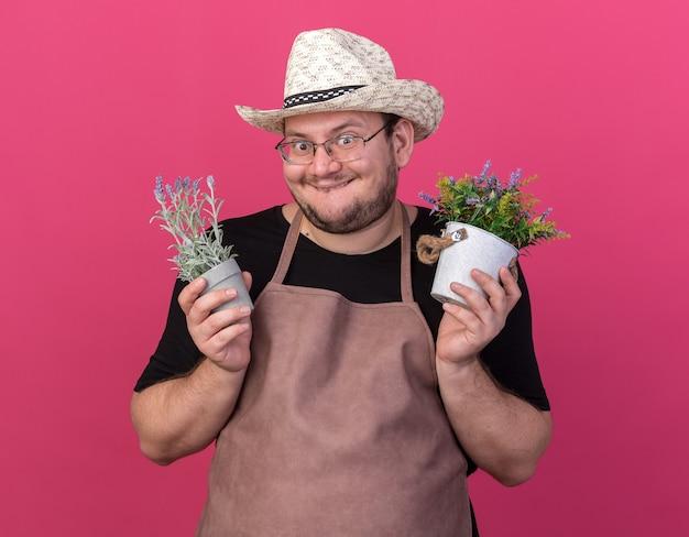 Opgewonden jonge mannelijke tuinman die tuinieren hoed draagt die bloemen in bloempotten houdt die op roze muur worden geïsoleerd
