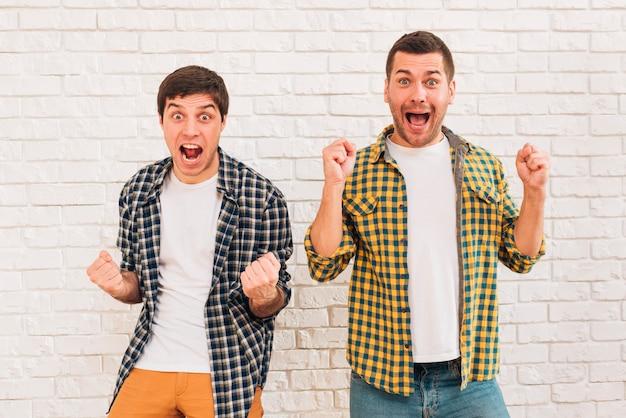 Opgewonden jonge mannelijke vrienden staan tegen witte bakstenen muur balde hun vuist