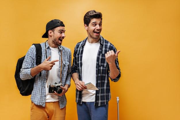 Opgewonden jonge mannen in geruite overhemden wijzen naar rechts en kijken verbaasd. reizigers houden kaartjes en retro camera op oranje muur.