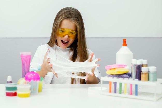 Opgewonden jonge meisjeswetenschapper die met slijm experimenteert