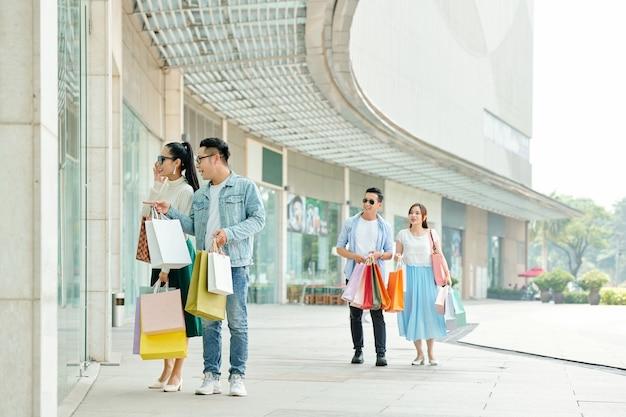 Opgewonden jonge mensen met papieren zakken kijken naar stijlvol kledingitem in etalage