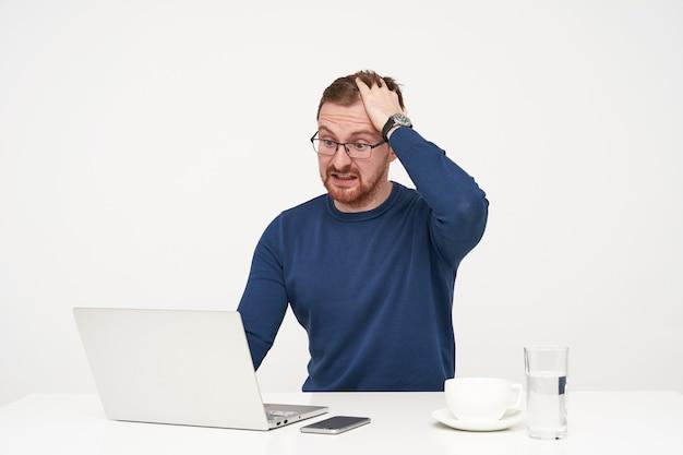 Opgewonden jonge mooie bebaarde man in glazen die zijn haar rimpelt terwijl hij verbaasd op zijn laptop kijkt, onverwacht nieuws leest terwijl hij op witte achtergrond zit