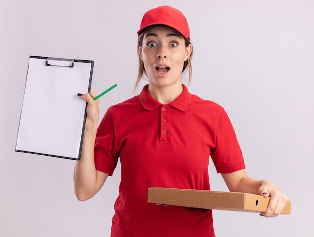 Opgewonden jonge mooie bezorger in uniform houdt klembord en pizzadoos geïsoleerd op een witte muur