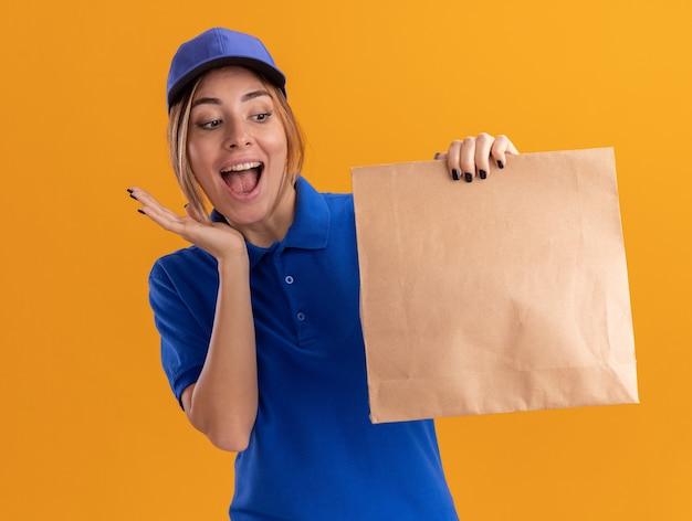 Opgewonden jonge mooie bezorgvrouw in uniform houdt en kijkt naar papierpakket geïsoleerd op een oranje muur