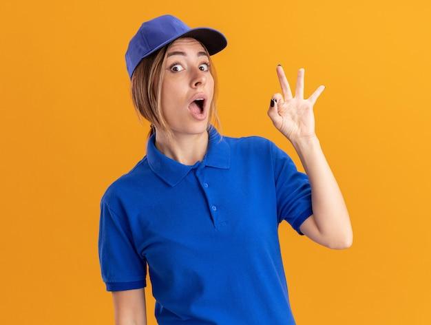 Opgewonden jonge mooie bezorgvrouw in uniforme gebaren ok handteken geïsoleerd op oranje muur