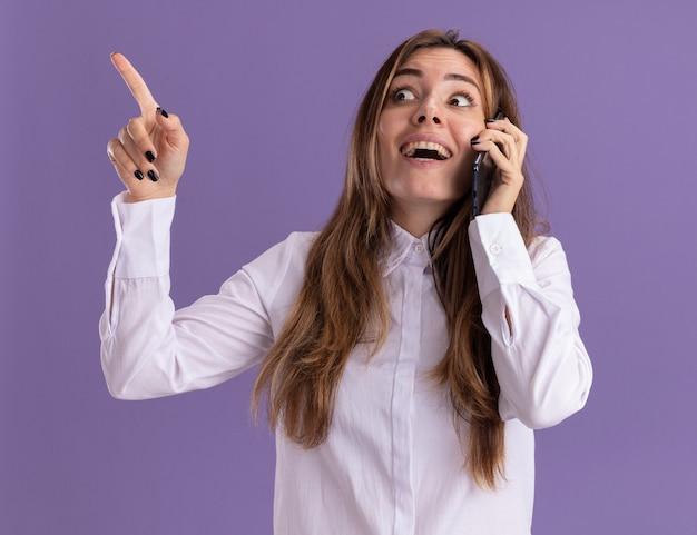 Opgewonden jonge, mooie blanke meid praat aan de telefoon en kijkt en wijst naar de zijkant