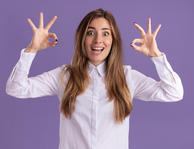 Opgewonden jonge, mooie blanke meisjesgebaren ok handteken met twee handen geïsoleerd op paarse muur met kopieerruimte