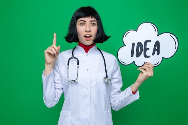 Opgewonden jonge, mooie blanke vrouw in doktersuniform met een stethoscoop die naar boven wijst en een ideebel vasthoudt