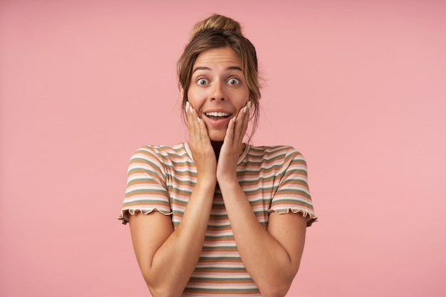 Opgewonden jonge mooie bruinharige dame die de handpalmen op haar wangen houdt terwijl ze opgewonden naar de camera kijkt met grote ogen geopend, geïsoleerd op roze achtergrond