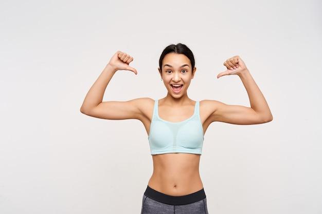 Opgewonden jonge mooie bruinharige sportieve dame met casual kapsel die verbaasd naar voren kijkt terwijl ze zichzelf beduimelt, staande over een witte muur