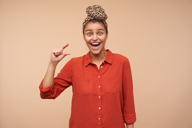 Opgewonden jonge mooie bruinharige vrouw die verbaasd naar voren kijkt en gelukkig lacht terwijl ze een klein formaat toont met opgeheven vingers, geïsoleerd over beige muur
