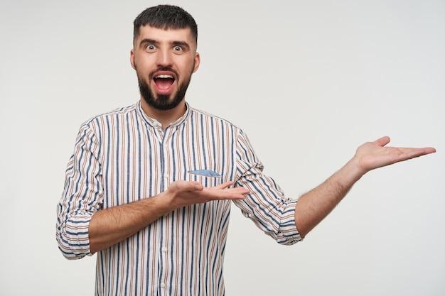 Opgewonden jonge mooie brunette bebaarde man met trendy kapsel zijn handen opheffen en kijken met grote ogen en mond geopend, staande over witte muur