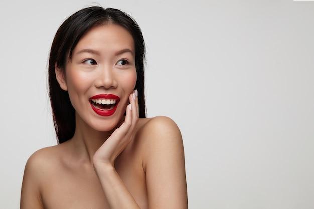 Opgewonden jonge mooie brunette vrouw met casual kapsel haar gezicht aan te raken met opgeheven hand en gelukkig opzij kijken, geïsoleerd over witte muur