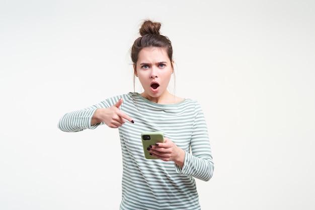 Opgewonden jonge mooie brunette vrouw met natuurlijke make-up wijzend met wijsvinger op haar mobiele telefoon terwijl ze verontwaardigd naar voren kijkt, geïsoleerd over witte muur