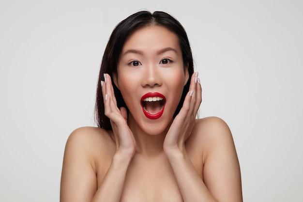 Opgewonden jonge mooie brunette vrouw met rode lippen met wijd geopende mond en handen opheffen naar haar gezicht, geïsoleerd over witte muur