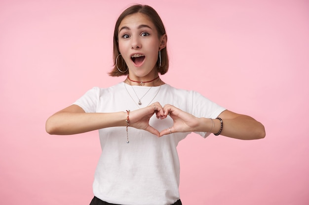 Opgewonden jonge mooie donkerharige vrouw met kort kapsel die zich met opgeheven handenhart vormt en emotioneel naar voren kijkt, geïsoleerd over roze muur
