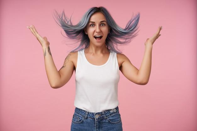 Opgewonden jonge mooie getatoeëerde vrouw met blauw wild haar kijkt opgewonden met brede mond open en houdt haar handen omhoog terwijl ze poseren op roze