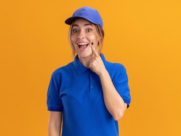Opgewonden jonge mooie levering meisje in uniform legt vinger op gezicht en kijkt naar de camera op oranje