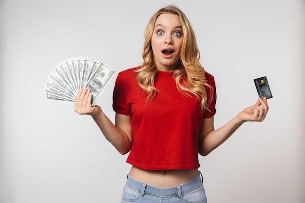 Opgewonden jonge mooie mooie vrouw poseren geïsoleerd over witte muur muur met geld en creditcard