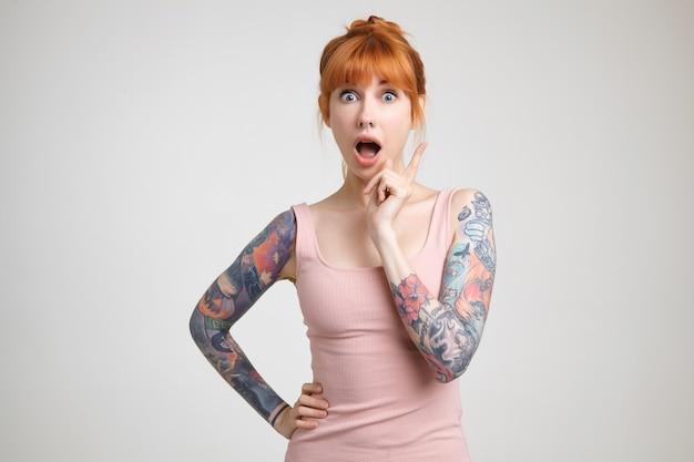 Opgewonden jonge mooie roodharige getatoeëerde dame camera kijken met grote ogen en mond geopend terwijl hand opsteken met idee teken, geïsoleerd op witte achtergrond