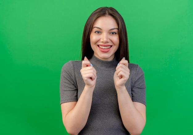 Opgewonden jonge mooie vrouw balde vuisten en pleiten voor iets geïsoleerd op groene achtergrond met kopie ruimte