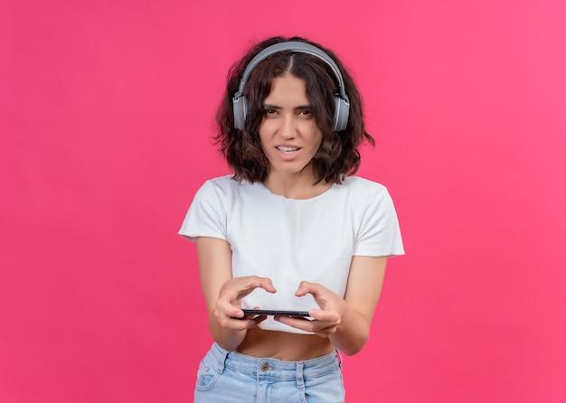 Opgewonden jonge mooie vrouw die hoofdtelefoons draagt en mobiele telefoon op roze muur met exemplaarruimte houdt