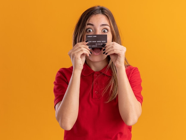 Opgewonden jonge mooie vrouw houdt creditcard geïsoleerd op oranje muur
