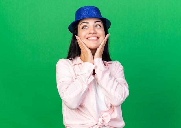 Opgewonden jonge mooie vrouw met feestmuts die handen op de wangen legt, geïsoleerd op een groene muur