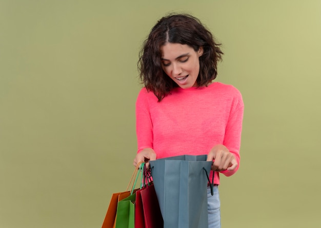 Opgewonden jonge mooie vrouw met kartonnen tassen en erin kijken op geïsoleerde groene muur met kopie ruimte