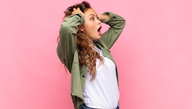 Opgewonden jonge mooie vrouw op roze achtergrond