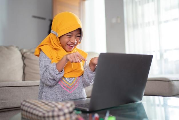 Opgewonden jonge moslimkind tijdens het online studeren vanuit huis met behulp van laptop
